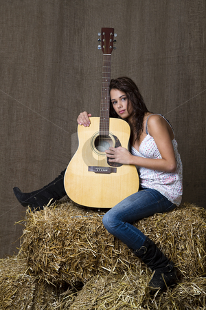 Young musician stock photo, young brunette girl leaning on accoustic guitar sitting on bales of straw by Yann Poirier