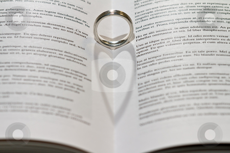 Heart shadow from ring stock photo, Ring casting heart shadow in book. by Gert Lavsen