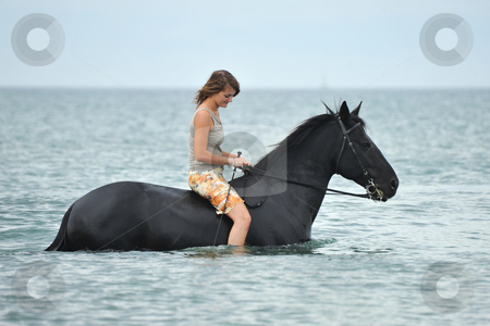 Woman and  horse in the sea stock photo, beautiful black  horse in the sea and beautiful woman by Bonzami Emmanuelle