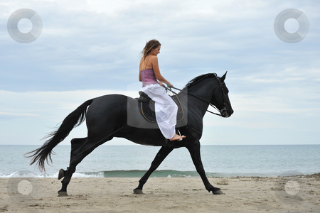 Woman and  horse on the beach stock photo, beautiful black  horse on the beach and beautiful woman by Bonzami Emmanuelle