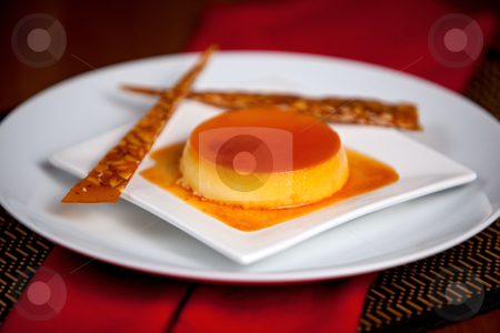 Flan stock photo, Creme caramel with nougatine strips on white plates. by Glenn Price