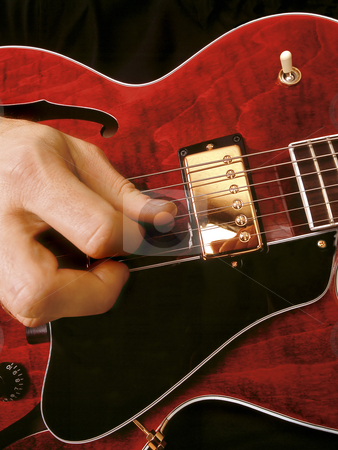 Electric guitar playing stock photo, Close-up of a jazz musician playing red electric guitar. by © Ron Sumners