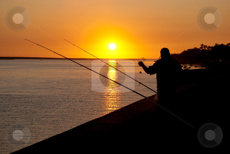 Man fishing on sunset  stock photo, Silhouette of man fishing on sunset in a dock near the river. by Homydesign