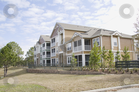 Multistory apartments stock photo, colorful multistory apartments in brown shades with stonework by Lee Barnwell