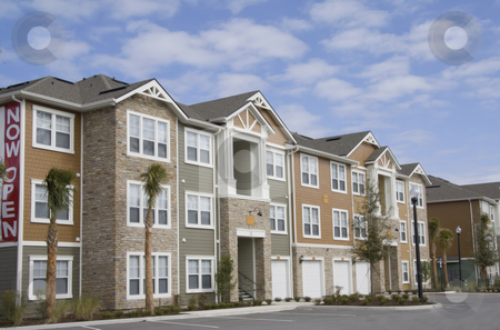 Upscale multistory apartments stock photo, upscale apartments with garages, stonework, variable siding material and a tropical landsaping by Lee Barnwell