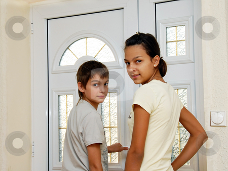 Boy and girl by door stock photo, teenage girl and boy by white front door smiling by Julija Sapic