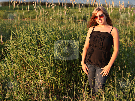 Portrait of a beautiful woman in grass stock photo, Beautiful woman in grass taken closeup in summer by Melissa King