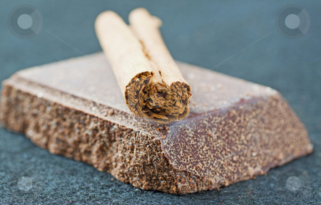 Chocolate and cinnamon stock photo, Piece of chocolate with piece of cinnamon by Fabio Alcini