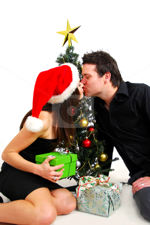 Couple by Christmas tree stock photo, Attractive couple celebrating Christmas by the tree with a kiss by Mornay Van Vuuren
