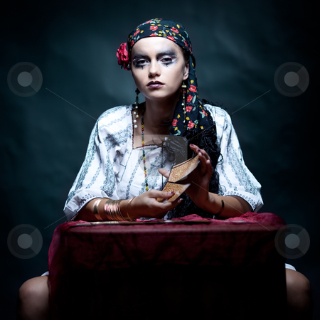 A portrait of a gypsy fortune teller mixing the tarot cards. stock photo, a portrait of a gypsy fortune teller, sitting at a table and mixing the tarot cards that she holds in her hands. she is looking at the camera. by dan comaniciu
