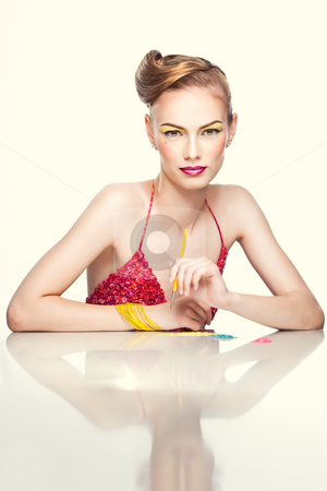 A colorful beauty portrait of a blonde, young woman stock photo, a studio beauty portrait of a young woman, with colorful makeup and clothes, shot on white background. She holds a makeup brush in one hand as she is trying on different eyeshadow colors.  by dan comaniciu