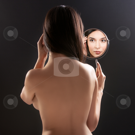A beauty image of a young woman looking into a mirror, smiling,  stock photo, a beauty studio picture of a young woman looking in a mirror, while her back is turned to the camera. the mirror held over her left shoulder reflects her smiling face. by dan comaniciu