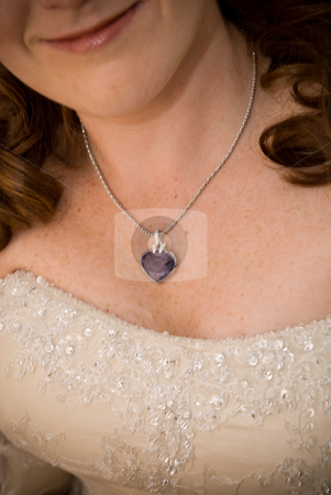Sexy bride showing her purple stoned necklace and cleavage stock photo, sexy red head bride showing her purple stoned necklace and cleavage by Ansunette
