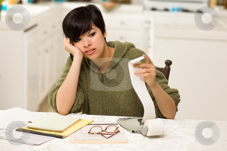 Multi-ethnic Young Woman Agonizing Over Financial Calculations stock photo, Multi-ethnic Young Woman Agonizing Over Financial Calculations in Her Kitchen. by Andy Dean