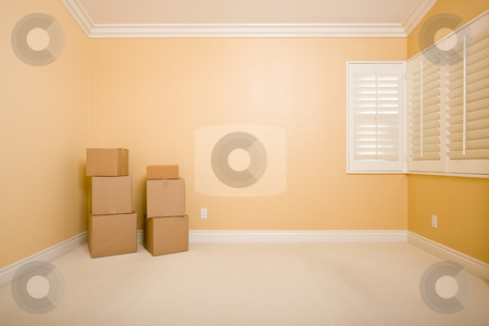 Moving Boxes in Empty Room with Copy Space on Wall stock photo, Moving Boxes in Empty Room with Copy Space on Blank Wall. by Andy Dean