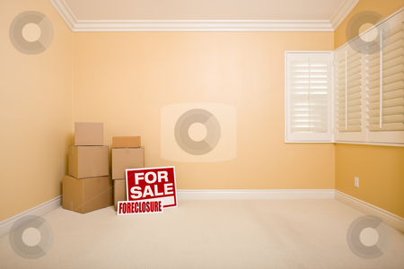 Boxes, Sale and Foreclosure Real Estate Signs in Empty Room stock photo, Moving Boxes, For Sale and Foreclosure Real Estate Signs on Floor in Empty Room with Copy Space on Blank Wall. by Andy Dean