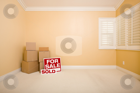 Boxes, Sale and Sold Real Estate Signs in Empty Room stock photo, Moving Boxes, For Sale and Sold Real Estate Signs on Floor in Empty Room with Copy Space on Blank Wall. by Andy Dean