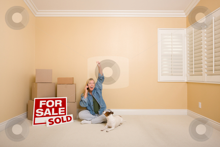 Sold Real Estate Signs, Boxes and Happy Woman on Phone stock photo, Pretty Woman Sitting on Floor Using Phone Celebrating Next to Moving Boxes, Sold Real Estate Signs and Dog in Empty Room. by Andy Dean
