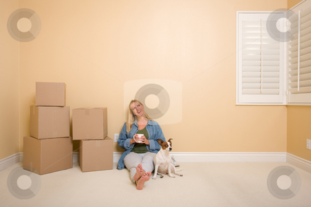 Relaxing Woman and Dog Next to Boxes on Floor stock photo, Pretty Woman Sitting on Floor with Cup Next to Moving Boxes and Dog in Empty Room. by Andy Dean