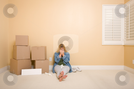Upset Woman on Floor Next to Boxes and Blank Sign stock photo, Upset Woman with Tissues on Floor Next to Boxes and Blank Sign in Empty Room. by Andy Dean