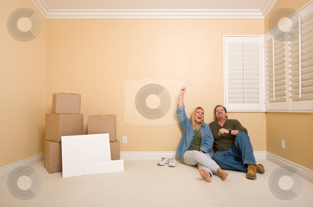 Couple on Floor Near Boxes and Blank Signs stock photo, Excited Couple Relaxing on Floor Near Boxes and Blank Real Estate Signs in Empty Room by Andy Dean