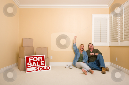Couple on Floor Near Boxes and Sold Real Estate Signs stock photo, Excited Couple Relaxing on Floor Near Boxes and Sold Real Estate Signs in Empty Room. by Andy Dean