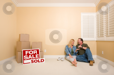 Couple on Floor Near Boxes and Sold Real Estate Signs stock photo, Excited Couple With New Keys Relaxing on Floor Near Boxes and Sold Real Estate Signs in Empty Room. by Andy Dean