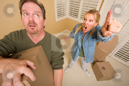 Stressed Man Moving Boxes for Demanding Wife stock photo, Stressed Man Moving Boxes for Demanding Wife Surrounded by Other Boxes. by Andy Dean