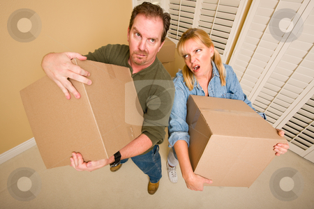 Exhausted Couple Holding Moving Boxes stock photo, Obviously Exhausted Couple Holding Moving Boxes in Empty Room. by Andy Dean