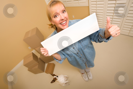 Woman and Doggy with Blank Sign Near Moving Boxes stock photo, Excited Woman with Thumbs Up and Doggy Holding Blank Sign Near Moving Boxes in Empty Room Taken with Extreme Wide Angle Lens.  by Andy Dean