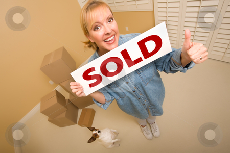 Woman and Doggy with Sold Sign Near Moving Boxes stock photo, Excited Woman with Thumbs Up and Doggy Holding Sold Real Estate Sign Near Moving Boxes in Empty Room Taken with Extreme Wide Angle Lens.  by Andy Dean