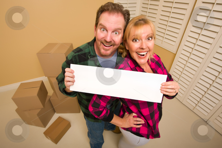 Happy Couple Holding Blank Sign in Room with Packed Boxes stock photo, Happy Goofy Couple Holding Blank Sign in Room with Packed Boxes. by Andy Dean