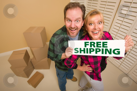 Goofy Couple Holding Free Shipping Sign Surrounded by Boxes stock photo, Goofy Couple Holding Free Shipping Sign in Room with Packed Cardboard Boxes. by Andy Dean