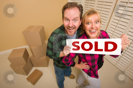 Goofy Couple Holding Sold Sign Surrounded by Boxes stock photo, Goofy Couple Holding Sold Sign in Room Surrounded by Cardboard Boxes. by Andy Dean