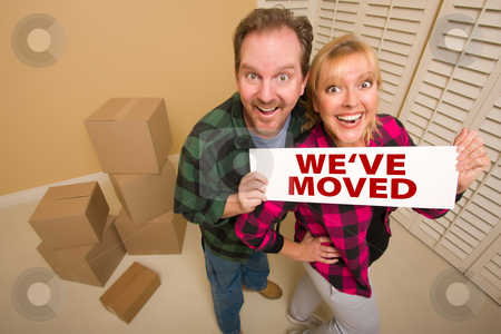 Goofy Couple Holding We've Moved Sign Surrounded by Boxes stock photo, Goofy Couple Holding We've Moved Sign in Room with Packed Cardboard Boxes. by Andy Dean