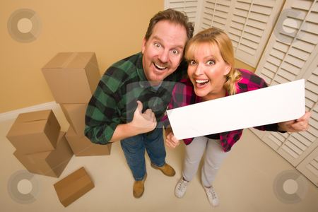Goofy Goofy Thumbs Up Couple Holding Blank Sign Surrounded by Bo stock photo, Goofy Thumbs Up Couple Holding Blank Sign in Room with Packed Cardboard Boxes. by Andy Dean