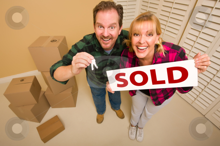 Goofy Couple Holding Key and Sold Sign Surrounded by Boxes stock photo, Goofy Couple Holding Key and Sold Sign in Room with Packed Cardboard Boxes. by Andy Dean