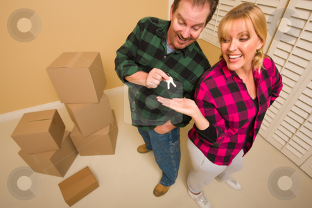 Goofy Excited Man Handing Keys to Smiling Wife stock photo, Goofy Excited Man Handing Keys to Smiling Wife in Room with Packed Boxes. by Andy Dean