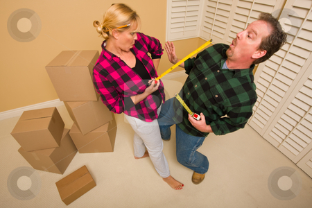 Couple Having Fun Sword Fight with Tape Measures stock photo, Couple Having a Fun Sword Fight with Their Tape Measures Surrounded by Packed Moving Boxes. by Andy Dean
