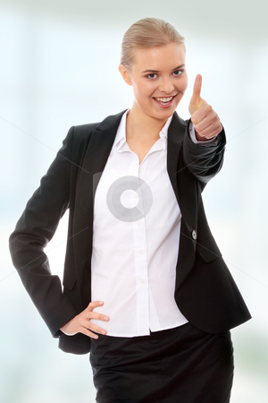Young business woman showing OK sign stock photo, Young business woman showing OK sign, looking at camera and smiling. by Piotr_Marcinski