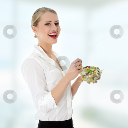 Businesswoman eating salad stock photo, Young businesswoman eating salad by Piotr_Marcinski