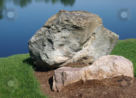 Boulder stock photo, Large Boulder with a lake background by Barb Hodanbosi