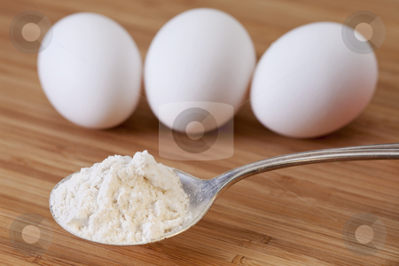 Flour and egss stock photo, baking ingredients concept - tablespoon of white wheat flour and three eggs on wooden (bamboo) board, selective focus by Marek Uliasz