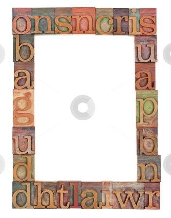 Alphabet frame in letterpress type stock photo, vertical alphabet frame - random vintage wood letterpress printing blocks surrounding white copy space by Marek Uliasz
