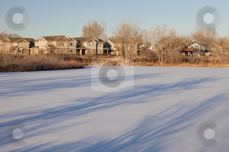 Houses and frozen lake in Colorado stock photo, housing development and lake natural area in Fort Collins, Colorado, afternoon winter scenery with long tree shadows by Marek Uliasz