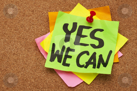 Yes we can stock photo, yes we can - motivational slogan on a stack of sticky notes posted on cork bulletin board by Marek Uliasz