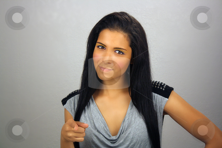 Beautiful Mischievous Teen Latina stock photo, A lovely teenage Latina with a mischievous or playful facial expression points her right index finger at you. by Carl Stewart