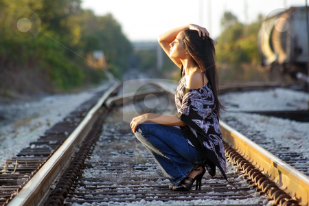 Beautiful Teen Latina on Railroad Tracks (2) stock photo, A lovely teenage Latina squats down on a railroad track, facing the sun with her eyes closed. by Carl Stewart