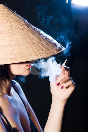 Woman in the Vietnamese hat stock photo, woman in the Vietnamese hat smoking a cigarette by Salauyou Yury
