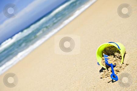 Toy bucket and shovel on an empty beach stock photo, Toy bucket and shovel on an empty beach by tish1
